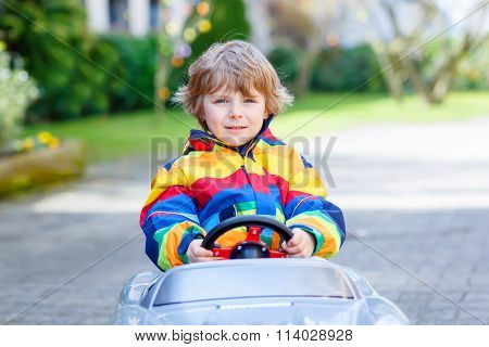 Little preschool boy driving big toy old vintage car, outdoors