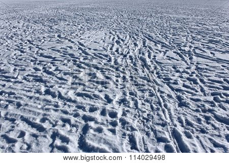 Footprints On Snowy Surface Of Frozen Pond