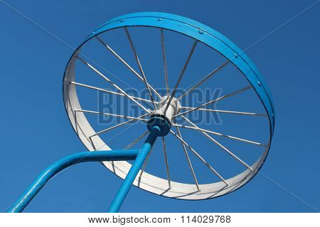 Metal Detail As A Bicycle Wheel Against The Sky