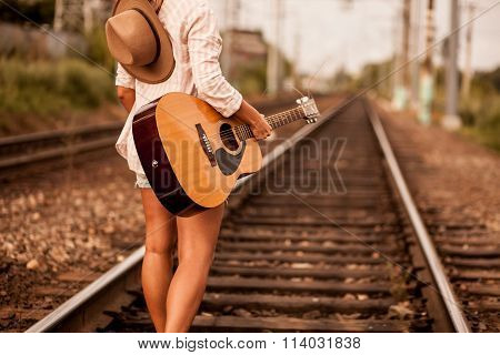 Girl walks alone the railway with guitar