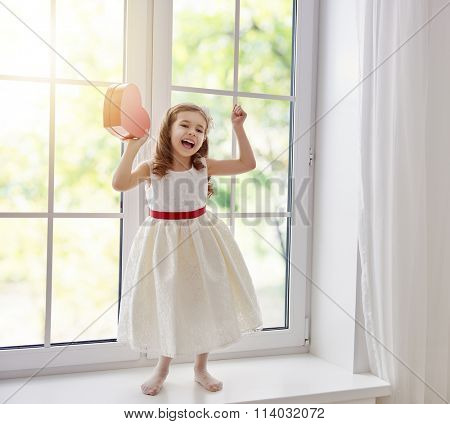 Sweet child girl with red heart. Little girl dancing on the window and holding gift box. Wedding, Valentine concept.