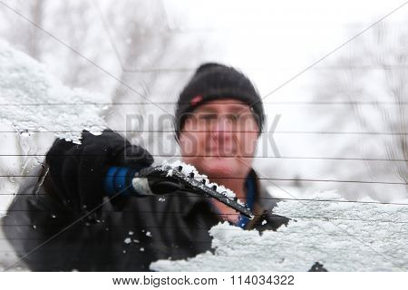 Man scraping snow and ice from car window , shot through wet window, shallow focus on scraper