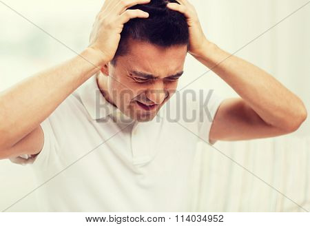 unhappy man suffering from head ache at home