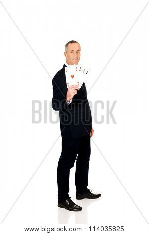Full length elegant business man with four aces