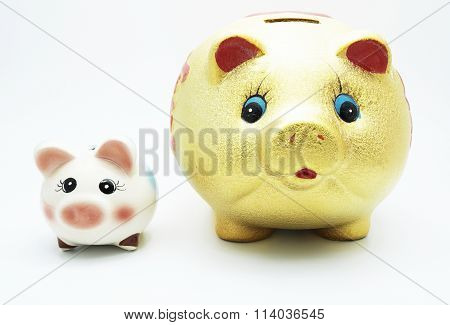 Big golden piggy bank and small colorful piggy bank, isolated on white background