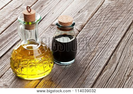 Olive oil and vinegar bottles on wooden table