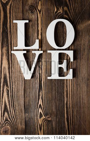 White letters forming word LOVE written on dark wooden background
