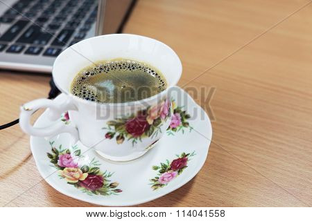 Cup of coffee and saucer with rose painting near laptop and wooden table