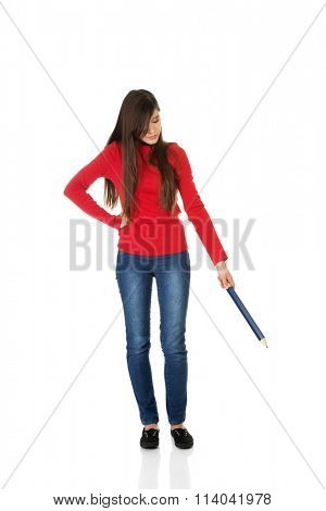 Beautiful woman pointing down with a big pencil.