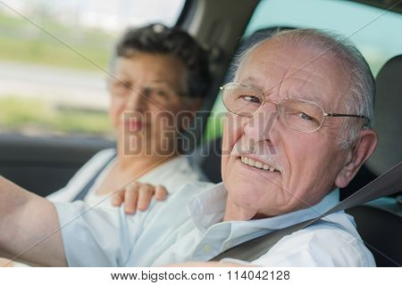 Elderly couple looking out through car window
