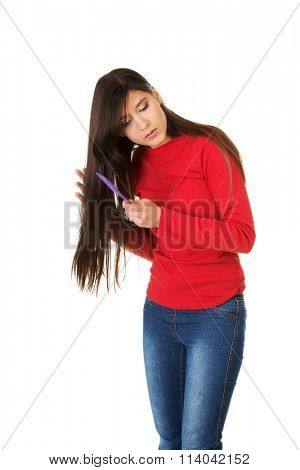 Woman combing her tangled hair.