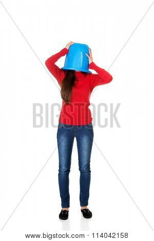 Woman with plastic bucket on head.