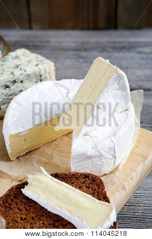 Camembert, Roquefort And Rye Bread Slices On A Cutting Board
