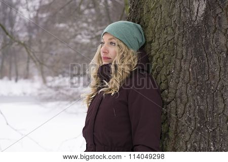 sad woman leaning against tree in winter