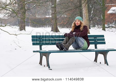 lonely woman sitting on park bench in winter