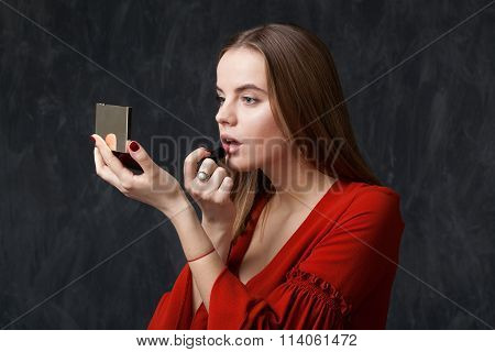 Woman Applying Lipstick Looking In To The Mirror