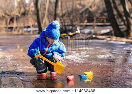 child playing with paper boats in spring water