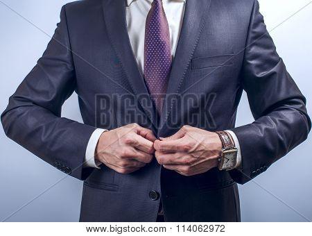 Man buttoning dark jacket