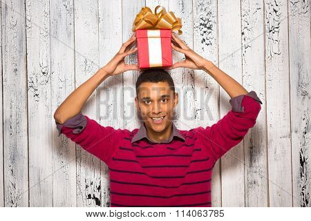 Young man posing with a present in studio
