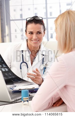 Close up of happy female brunette doctor with glasses at medical office with patient, smiling, x-ray image in hand, wearing stethoscope and lab coat.