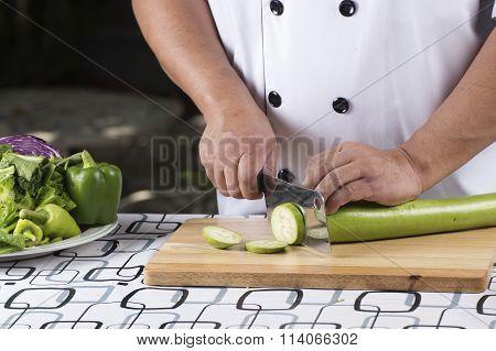 Chef Slicing Green Eggplant