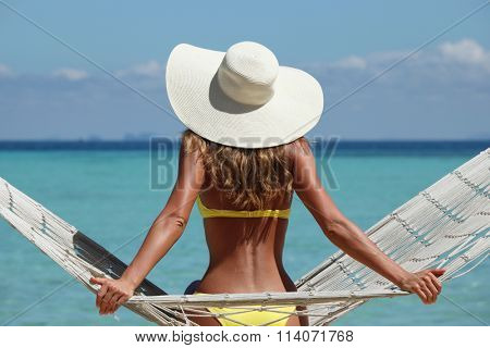 Rear view of a woman in bikini with a stylish hat sitting on a hammock on a beach by the sea