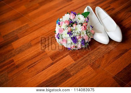 Wedding bouquet with violet flowers and white bride's wedding shoes on the parquet floor, room for c
