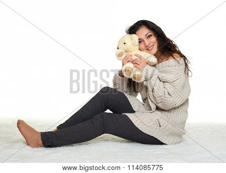 girl with teddy bear sit on fur, white background