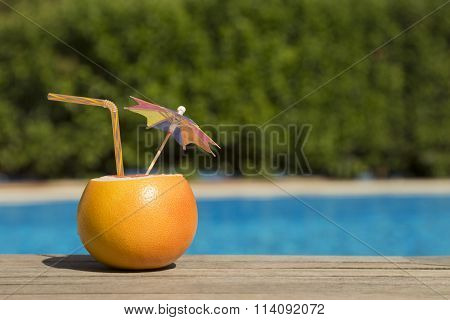 Grapefruit with drinking straw and paper umbrella at the poolside