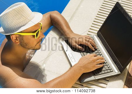 Young male working on laptop from a swimming pool