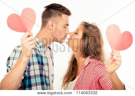 Cheerful Couple In Love Holding Two Paper Hearts Kissing Each Other
