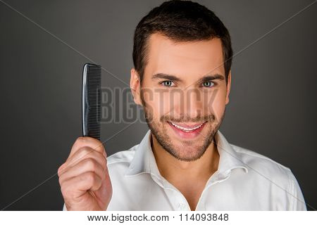Cheerful Man Holding A Comb
