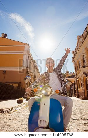 Nice boy in glasses with moped and smiling