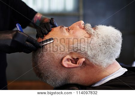 portrait of senior bearded man in barbershop. barber shaving man with straight razor