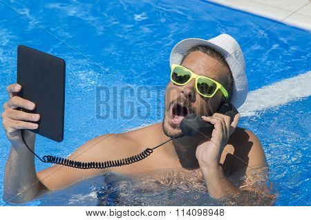 Guy having a call from a swimming pool