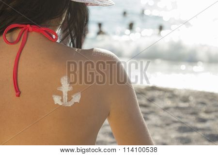 Female on a beach with sun cream anchor drawing on her back