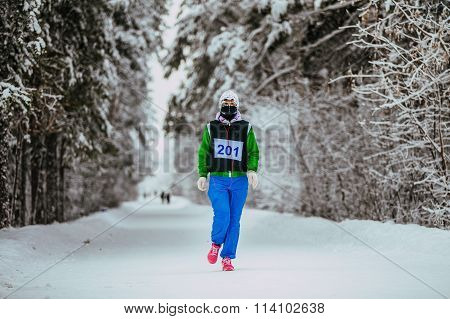 girl athlete running snow-covered alley in winter Park