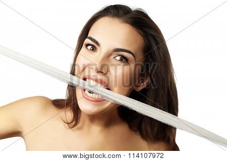 Young beautiful woman tearing gauze with her teeth, isolated on white