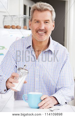 Mature Man Adding Sugar To Cup Of Coffee
