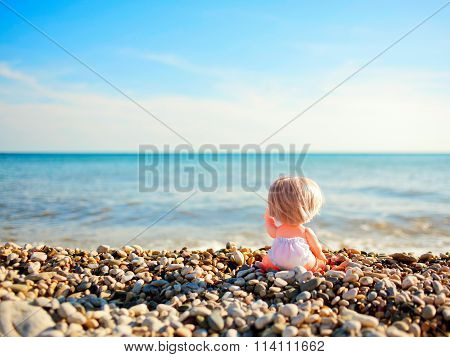 Doll Sitting On Beach And Pointing To The Sea