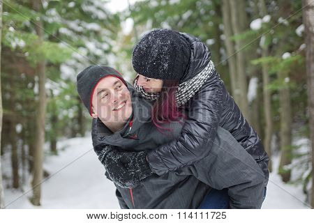 Winter couple piggyback in snow smiling happy and excited.