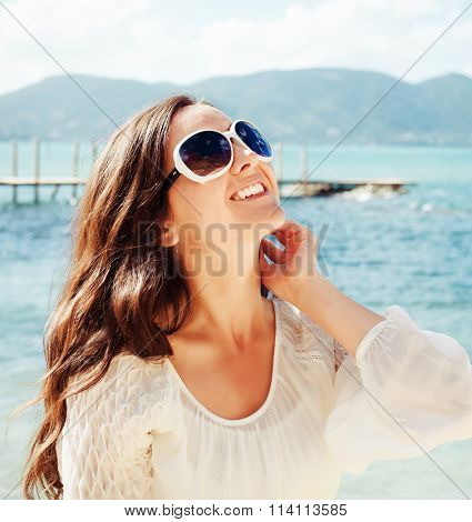Happy woman in summer white dress on beach.