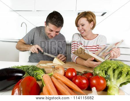 American Couple Working In Domestic Kitchen Together Wife Following Recipe In Cookbook And Husband S