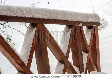wooden patio deck railing covered in snow