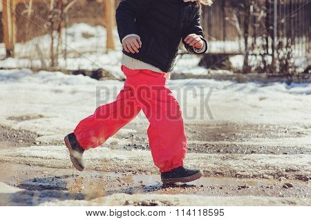 child girl in waterproof pants running and jumping in puddle on early spring walk