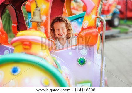 happy child girl riding train on funfair on summer vacation