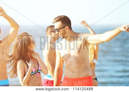 Happy couple and their playful friends relaxing at the beach, outdoors
