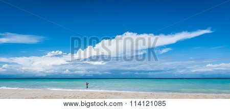 Man in the surf.  Warm afternoon on the beach in Cuba.  A man walks in the gentle ocean surf in Vara