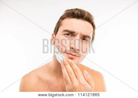 A Young Handsome Man Shaves In Front Of Camera