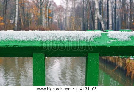 Snow And Rain On Green Wooden Railing. Fragment.